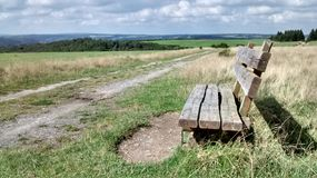 Wanderlust. In countryside. Wooden bench waiting for hiking people Stock Photography