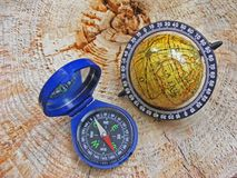 Wanderlust - globe and compass. On wooden background Royalty Free Stock Images