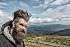 Wanderlust and hiking. Travel and adventure. Man with long beard and mustache outdoor. Hipster with bearded face at mountains. Guy or bearded man at cold Royalty Free Stock Image