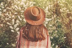 Wanderlust. hipster girl in hat and poncho with amazing hair wit. H flowers standing in park in evening sunshine. back of stylish woman traveler in spring garden Royalty Free Stock Photography