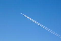 Wanderlust. Large passenger plane with contrails in the blue sky Stock Images