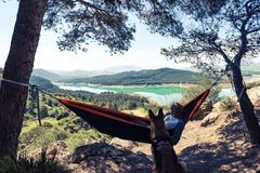 Wanderlust man and dog relaxing at hammock in mountains.  Stock Image