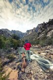 Wanderlust man and dog in wild mountains by the river.  Stock Photography