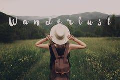 Wanderlust text sign concept, hipster traveler woman holding hat Stock Photos