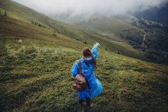 Wanderlust and travel concept. girl traveler in raincoat with ba. Ckpack walking in clouds in mountains. stylish hipster woman exploring. space for text Stock Image