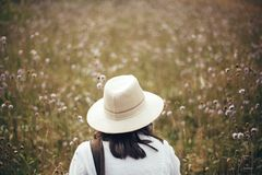 Wanderlust and travel concept. Hipster girl with backpack traveling in sunny mountains, walking in  wildflower meadow. Stylish stock photo