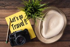 Wanderlust - travel concept.Let`s go travel. Wanderlust - travel concept.camera,hat,pencil and note `let`s go travel` on wooden background Royalty Free Stock Photos