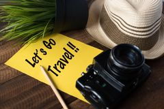 Wanderlust - travel concept.Let`s go travel. Wanderlust - travel concept.camera,hat,pencil and note `let`s go travel` on wooden background Royalty Free Stock Photography