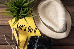 Wanderlust - travel concept.let`s go travel. Wanderlust - travel concept.camera,hat,sunglass,plant,pencil and note `let`s go` on wooden background Stock Photos