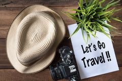 Wanderlust - travel concept.Let`s go travel. Wanderlust - travel concept.camera,plant,hat and note `let`s go travel` on wooden background Royalty Free Stock Photo