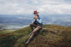 Wanderlust and travel concept. man traveler in hat with photo ca. Mera sitting on top of mountains. stylish hipster taking photo. space for text. atmospheric Stock Image