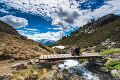Wanderluster hiker sitting with dog in mountains. On wooden bridge Stock Photos