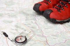 Wandern der benutzten Schuhe und des Kompassses auf Karte stockfotos