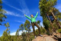 Wandern der Frau, die den Gipfel zujubelt im Wald erreicht Stockfotografie