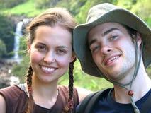 Wandern der Paare mit Wasserfall Stockfotos