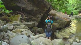 Wandern der Schönheit mit dem Rucksack, der Foto durch Smartphone auf Gebirgsfluss mit Flusssteinen und grünem Moos im Dschungel  stock video footage