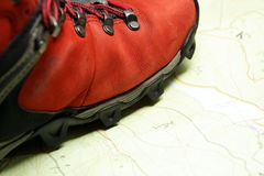Wandern der Schuhe auf Karte der Berge stockbild