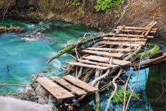 Wandern des Fußwegs durch szenische schöne alte hölzerne Bohlenbrücke über sauberem Gebirgsstrom mit klarem Türkiswasser tranquil lizenzfreie stockfotografie