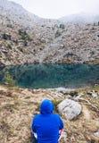 Wandern des Mannes in den Bergen, die in der Front zu einem stillen See I sich entspannen stockfotografie