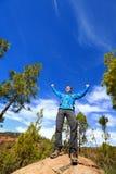 Wandern des Mannes, der die Gipfelspitze zujubelt im Wald erreicht Stockfotografie