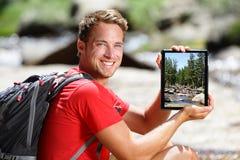 Wandern des Mannes, der Naturwaldbild auf Tablette zeigt Stockbilder