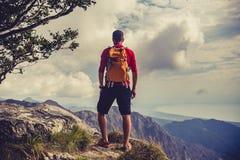 Wandern des Mannes oder des Hinterläufers in Anspornungsbergen Stockfotografie