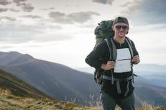 Wandern des Mannes oder des Hinterläufers in den Bergen, inspirierend Landschaft Motivierter Wanderer mit dem Rucksack, der Bergb Stockfoto