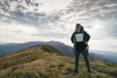 Wandern des Mannes oder des Hinterläufers in den Bergen, inspirierend Landschaft Motivierter Wanderer mit dem Rucksack, der Bergb Stockfotografie