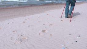 Wandern Sie mit den Wanderstöcken, die auf sandigen Strand nahe Meer gehen stock video