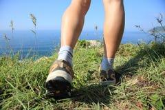 Wandern von Beinen mit verletztem Knie auf Küstenberg Stockfotografie