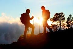 Wandern von den Paaren, die Sonnenuntergangansicht über Wanderung genießend schauen Lizenzfreie Stockfotos
