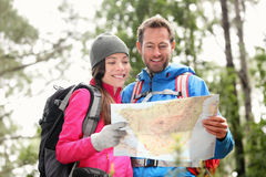 Wandern von den Paaren, welche die Karte wandert im Wald betrachten Lizenzfreies Stockfoto