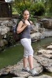 Wandern von Frauenquerfluß mit Reisetasche stockfoto