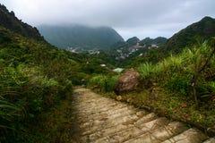 Wanderweg, der in die Berge von Jiufen, Taiwan mit Berg Keelung eingehüllt in Wolken im Hintergrund führt lizenzfreie stockfotografie