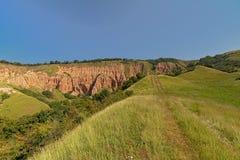 Wanderweg im Gras in Richtung zum Rock geologischer Bildung Rapa Rosie, der Grand Canyon von Rumänien, unter einem klaren blauen  lizenzfreie stockbilder