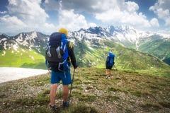 Wanderweg mit Touristen im Gebirgszug Trekking in den Bergen Wanderung mit zwei Wanderern auf schneebedeckten Hochländern stockfoto