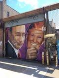 Wandgemälde von Putin eine Maske von Donald Trump halten stockbilder