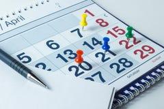 Wandkalender und Stift, wichtige Tage werden mit knops markiert lizenzfreies stockbild