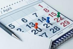 Wandkalender und Stift, wichtige Tage werden mit knops markiert stockfoto