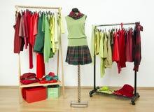 Wandschrank mit den ergänzenden Farben rot und grüner Kleidung kleiden. Stockfotografie