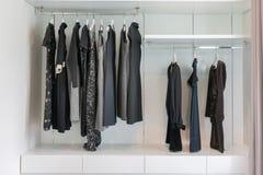Wandschrank mit der Reihe des schwarzen Kleides hängend am Kleiderbügel Lizenzfreies Stockbild