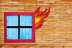 Wandziegelstein mit Fenster im Feuer Stockbilder