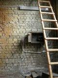 Wandziegelstein mit Strichleiter und Drähten Lizenzfreies Stockfoto