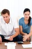 Wanhopig paar dat hun rekeningen bekijkt stock fotografie
