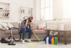 Wanhopig vrouwen schoonmakend huis met veel hulpmiddelen royalty-vrije stock foto
