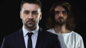 Wanhopige bedrijfsmens die aan Jesus Christ op achtergrond bidden, die om hulp vragen stock video