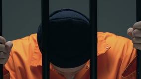 Wanhopige gevangene met littekens op de bars van de gezichtsbewaarcel, doodstrafwachten stock footage