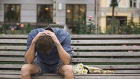 Wanhopige jonge mensenzitting alleen op bank, die aan depressie na verbreken lijden stock fotografie