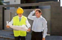 Wanhopige klant in spanning en de arbeider van de aannemersvoorman met helm en vest die in openlucht op nieuwe woningbouwblauwdru Royalty-vrije Stock Afbeelding
