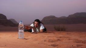 Wanhopige mens in de woestijn die naar water snakken Royalty-vrije Stock Foto's